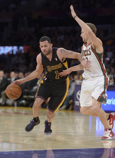 Dec 31, 2013; Los Angeles, CA, USA; Los Angeles Lakers guard Jordan Farmar (1) is defended by Milwaukee Bucks guard Luke Ridnour (13) during the game at Staples Center. The Bucks defeated the Lakers 94-79. Mandatory Credit: Kirby Lee-USA TODAY Sports