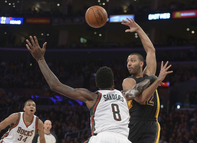 Dec 31, 2013; Los Angeles, CA, USA; Los Angeles Lakers guard Kendall Marshall (12) is defended by Milwaukee Bucks center Larry Sanders (8) during the game at Staples Center. The Bucks defeated the Lakers 94-79. Mandatory Credit: Kirby Lee-USA TODAY Sports