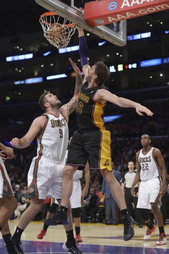 Dec 31, 2013; Los Angeles, CA, USA; Los Angeles Lakers forward Pau Gasol (16) dunks the ball against Milwaukee Bucks center Miroslav Radjuljica (9) at Staples Center. The Bucks defeated the Lakers 94-79. Mandatory Credit: Kirby Lee-USA TODAY Sports