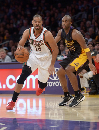 Dec 31, 2013; Los Angeles, CA, USA; Milwaukee Bucks guard Gary Neal (12) is defended by Los Angeles Lakers guard Jodie Meeks (20) at Staples Center. Mandatory Credit: Kirby Lee-USA TODAY Sports