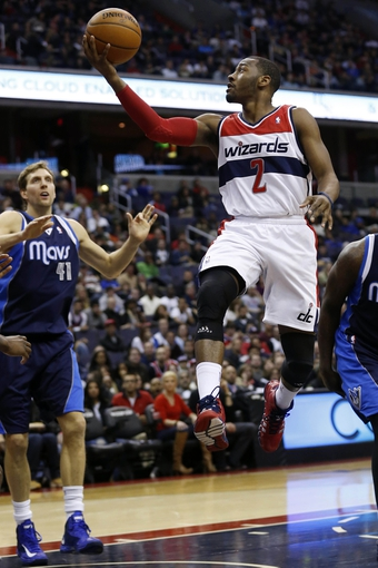 Jan 1, 2014; Washington, DC, USA;  Washington Wizards point guard John Wall (2) shoots the ball as Dallas Mavericks power forward Dirk Nowitzki (41) looks on in the second quarter at Verizon Center. Mandatory Credit: Geoff Burke-USA TODAY Sports