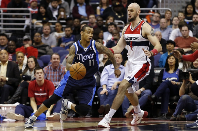 Jan 1, 2014; Washington, DC, USA;  Dallas Mavericks shooting guard Monta Ellis (11) dribbles the ball as Washington Wizards center Marcin Gortat (4) defends in the second quarter at Verizon Center. Mandatory Credit: Geoff Burke-USA TODAY Sports