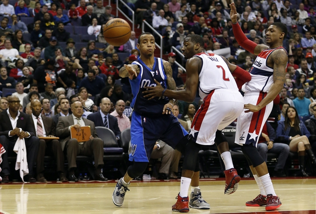 Jan 1, 2014; Washington, DC, USA;  Dallas Mavericks shooting guard Monta Ellis (11) passes the ball past Washington Wizards point guard John Wall (2) in the third quarter at Verizon Center. The Mavericks won 87-78. Mandatory Credit: Geoff Burke-USA TODAY Sports