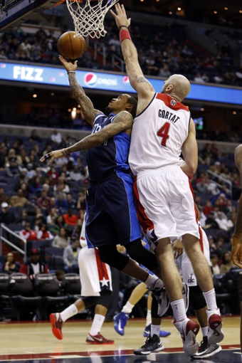 Jan 1, 2014; Washington, DC, USA;  Dallas Mavericks shooting guard Monta Ellis (11) shoots the ball  as Washington Wizards center Marcin Gortat (4) defends in the third quarter at Verizon Center. The Mavericks won 87-78. Mandatory Credit: Geoff Burke-USA TODAY Sports