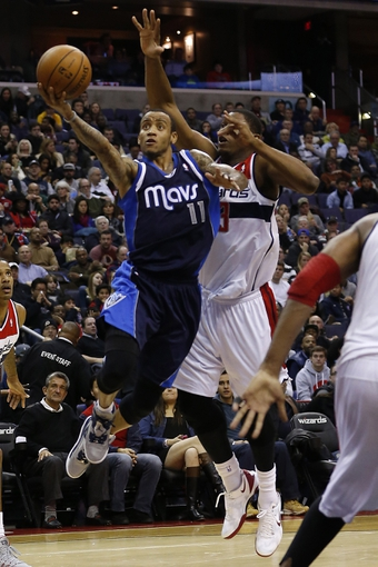 Jan 1, 2014; Washington, DC, USA;  DDallas Mavericks shooting guard Monta Ellis (11) shoots the ball as Washington Wizards shooting guard Bradley Beal (3) defends in the third quarter at Verizon Center. The Mavericks won 87-78. Mandatory Credit: Geoff Burke-USA TODAY Sports