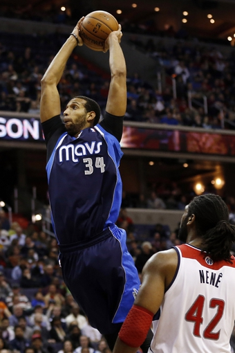 Jan 1, 2014; Washington, DC, USA;  Dallas Mavericks power forward Brandan Wright (34) dunks the ball as Washington Wizards power forward Nene Hilario (42) watches in the third quarter at Verizon Center. The Mavericks won 87-78. Mandatory Credit: Geoff Burke-USA TODAY Sports