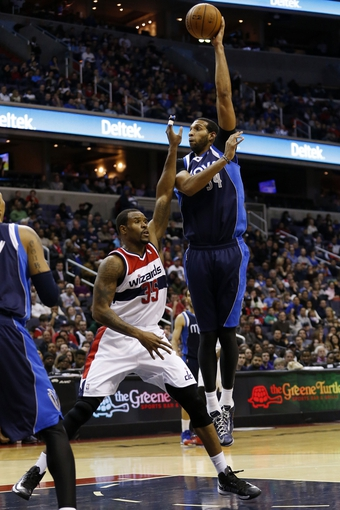 Jan 1, 2014; Washington, DC, USA;  Dallas Mavericks power forward Brandan Wright (34) shoots the ball over Washington Wizards power forward Trevor Booker (35) in the fourth quarter at Verizon Center. The Mavericks won 87-78. Mandatory Credit: Geoff Burke-USA TODAY Sports