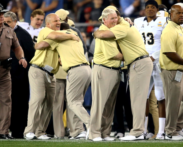 Jan 1, 2014; Glendale, AZ, USA; Central Florida Knights head coach George O'Leary (right) celebrates with an assistant coach in the closing seconds of the game against the Baylor Bears during the Fiesta Bowl at University of Phoenix Stadium. Central Florida defeated Baylor 52-42. Mandatory Credit: Mark J. Rebilas-USA TODAY Sports