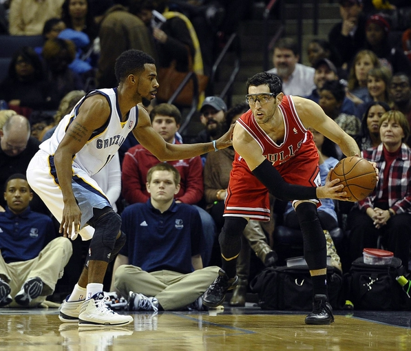 Dec 30, 2013; Memphis, TN, USA; Memphis Grizzlies point guard Mike Conley (11) guards Chicago Bulls shooting guard Kirk Hinrich (12) during the first quarter  at FedEx Forum. Chicago Bulls beat the Memphis Grizzlies 95 - 91. Mandatory Credit: Justin Ford-USA TODAY Sports