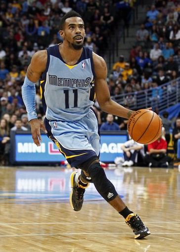 Jan 3, 2014; Denver, CO, USA; Memphis Grizzlies point guard Mike Conley (11) controls the ball in the second quarter against the Denver Nuggets at the Pepsi Center. Mandatory Credit: Isaiah J. Downing-USA TODAY Sports