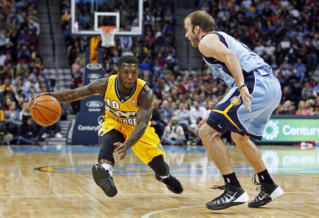 Jan 3, 2014; Denver, CO, USA; Memphis Grizzlies shooting guard Nick Calathes (12) guards Denver Nuggets point guard Nate Robinson (10) in the third quarter at the Pepsi Center. The Nuggets won 111-108. Mandatory Credit: Isaiah J. Downing-USA TODAY Sports