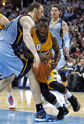 Jan 3, 2014; Denver, CO, USA; Memphis Grizzlies center Kosta Koufos (41) fouls Denver Nuggets point guard Nate Robinson (10) in the fourth quarter at the Pepsi Center. The Nuggets won 111-108. Mandatory Credit: Isaiah J. Downing-USA TODAY Sports