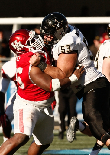 Jan 4, 2014; Birmingham, AL, USA; Houston Cougars defensive lineman Jeremiah Farley (96)  blocks  Vanderbilt Commodores offensive lineman Jake Bernstein (53) during the 2014 Compass Bowl at Legion Field. The Commodores defeated the Cougars 41-24. Mandatory Credit: Marvin Gentry-USA TODAY Sports