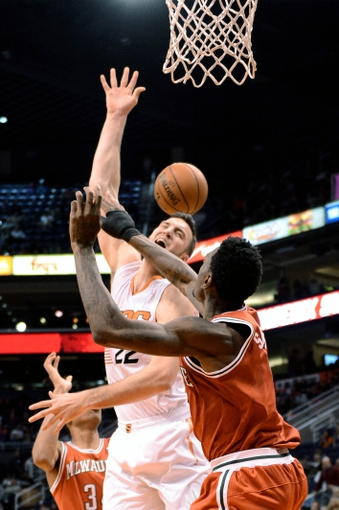 Jan 4, 2014; Phoenix, AZ, USA; Phoenix Suns forward Miles Plumlee (22) is fouled by Milwaukee Bucks center Larry Sanders (8) in the second half at US Airways Center. The Suns won 116-100. Mandatory Credit: Jennifer Stewart-USA TODAY Sports