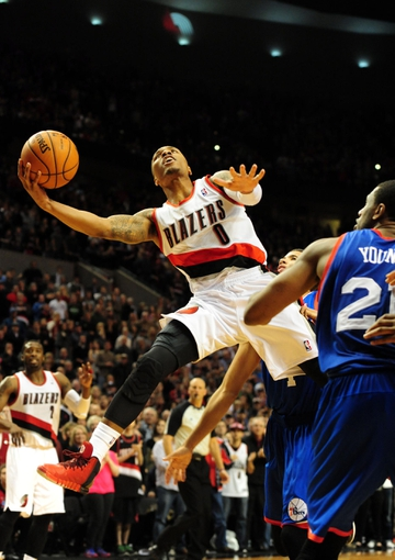 Jan. 04, 2014; Portland, OR, USA; Portland Trail Blazers point guard Damian Lillard (0) drives to the basket on Philadelphia 76ers power forward Thaddeus Young (21) late in the fourth quarter of the game at the Moda Center. Lillard missed the shot as the Sixers won the game 101-99. Mandatory Credit: Steve Dykes-USA TODAY Sports