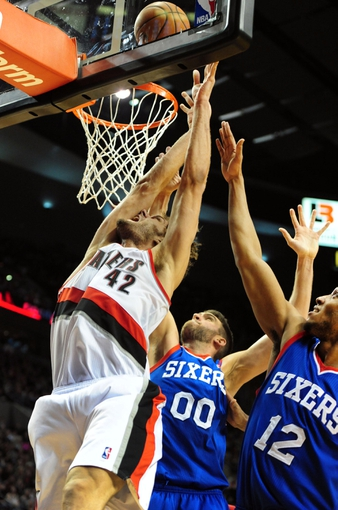 Jan. 04, 2014; Portland, OR, USA; Portland Trail Blazers center Robin Lopez (42) drives to the basket on Philadelphia 76ers center Spencer Hawes (00) and small forward Evan Turner (12)during the fourth quarter of the game at the Moda Center. The Sixers won the game 101-99. Mandatory Credit: Steve Dykes-USA TODAY Sports