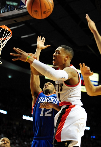 Jan. 04, 2014; Portland, OR, USA; Portland Trail Blazers point guard Damian Lillard (0) has his shot blocked from behind as he drives to the basket on Philadelphia 76ers small forward Evan Turner (12) during the fourth quarter of the game at the Moda Center. The Sixers won the game 101-99. Mandatory Credit: Steve Dykes-USA TODAY Sports