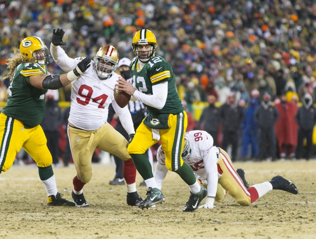Jan 5, 2014; Green Bay, WI, USA; Green Bay Packers quarterback Aaron Rodgers (12) scrambles with the football during the fourth quarter of the 2013 NFC wild card playoff football game against the San Francisco 49ers at Lambeau Field.  San Francisco won 23-20.  Mandatory Credit: Jeff Hanisch-USA TODAY Sports