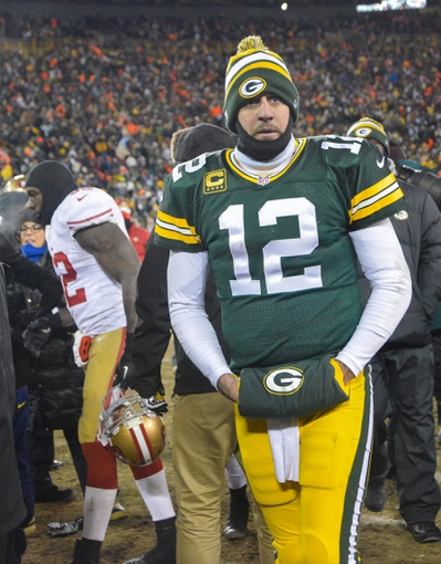 Jan 5, 2014; Green Bay, WI, USA;  Green Bay Packers quarterback Aaron Rodgers (12) walks off the field after the San Francisco 49ers beat the Packers 23-20 during the 2013 NFC wild card playoff football game at Lambeau Field. Mandatory Credit: Benny Sieu-USA TODAY Sports