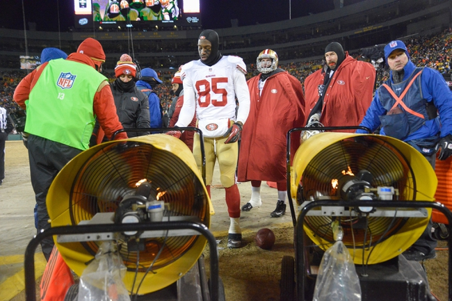 Jan 5, 2014; Green Bay, WI, USA;  San Francisco 49ers tight end Vernon Davis (85) stays warm on the sidelines by the heaters during the game against the Green Bay Packers in the 2013 NFC wild card playoff football game at Lambeau Field. Mandatory Credit: Benny Sieu-USA TODAY Sports