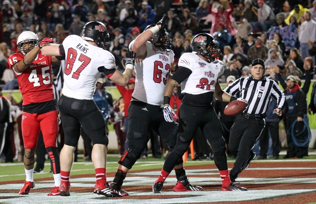 Jan 5, 2014; Mobile, AL, USA; Arkansas State Red Wolves running back Sirgregory Thornton (21) is congratulated by offensive linesman Cliff Mitchell (63) and teammates after scoring a touchdown in the first half at Ladd-Peebles Stadium. Mandatory Credit: Crystal LoGiudice-USA TODAY Sports