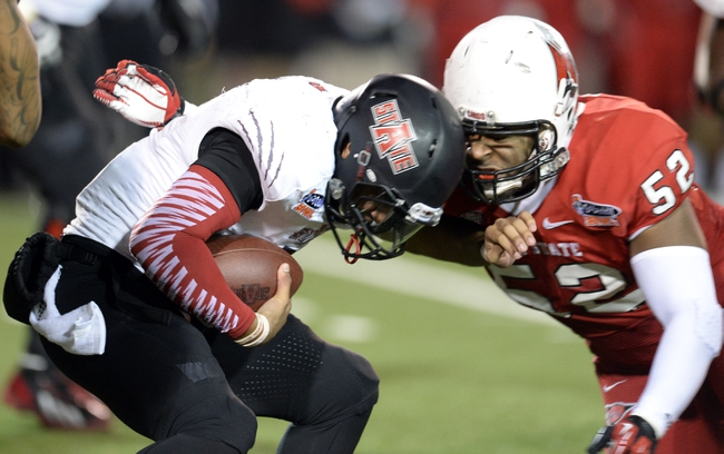 Jan 5, 2014; Mobile, AL, USA;  Arkansas State Red Wolves linebacker Quanterio Heath (52) gets wrapped up by Ball State Cardinals defensive end Nick Miles (52) during the fourth quarter at Ladd-Peebles Stadium. Mandatory Credit: John David Mercer-USA TODAY Sports