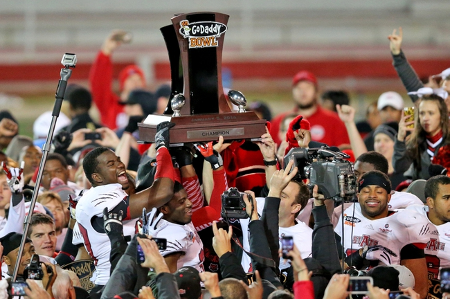 Jan 5, 2014; Mobile, AL, USA; Arkansas State Red Wolves defensive lineman Darius Dunaway (left) and teammates lift up the trophy after defeating the Ball State Cardinals 23-20 at Ladd-Peebles Stadium. Mandatory Credit: Crystal LoGiudice-USA TODAY Sports