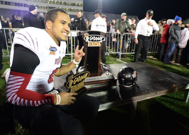 Jan 5, 2014; Mobile, AL, USA;  Arkansas State Red Wolves quarterback Fredi Knighten (9) poses with the Go Daddy trophy after their 23-20 victory over the Ball State Cardinals at Ladd-Peebles Stadium. Mandatory Credit: John David Mercer-USA TODAY Sports