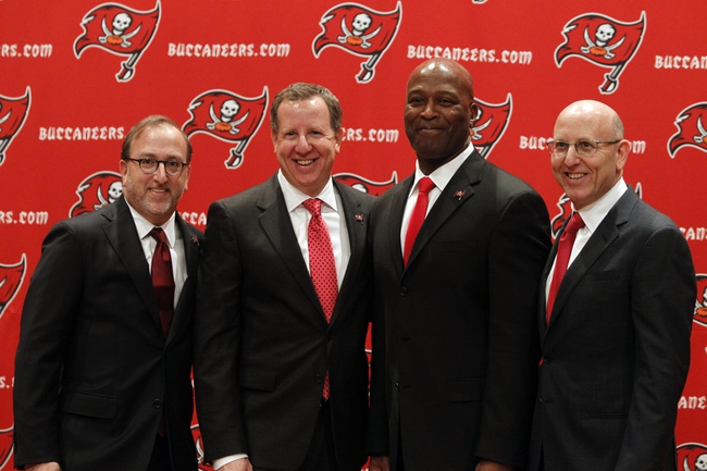 Jan 6, 2014; Tampa, FL, USA; Tampa Bay Buccaneers head coach Lovie Smith (second from right) poses with owners from left Edward Glazer , Bryan Glazer and Joel Glazer during a press conference at One Buccaneer Place. Mandatory Credit: Kim Klement-USA TODAY Sports