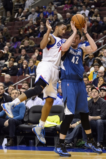 Jan 6, 2014; Philadelphia, PA, USA; Philadelphia 76ers guard Evan Turner (12) fouls Minnesota Timberwolves forward Kevin Love (42) during the third quarter at the Wells Fargo Center. The Timberwolves defeated the Sixers 126-95. Mandatory Credit: Howard Smith-USA TODAY Sports