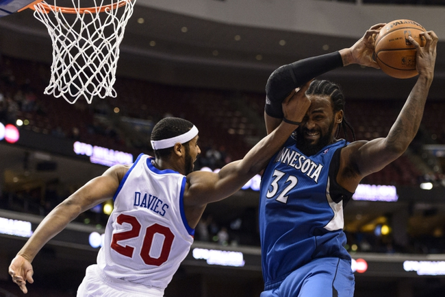Jan 6, 2014; Philadelphia, PA, USA; Minnesota Timberwolves center Ronny Turiaf (32) pulls down a rebound under pressure from Philadelphia 76ers forward Brandon Davies (20) during the fourth quarter at the Wells Fargo Center. The Timberwolves defeated the Sixers 126-95. Mandatory Credit: Howard Smith-USA TODAY Sports