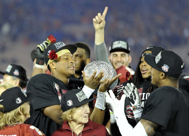 Jan 6, 2014; Pasadena, CA, USA; Florida State Seminoles quarterback Jameis Winston (left) hands the Coaches Trophy to defensive back P.J. Williams (right)  after the 2014 BCS National Championship game against the Auburn Tigers at the Rose Bowl.  Mandatory Credit: Kirby Lee-USA TODAY Sports