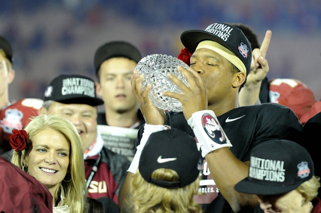 Jan 6, 2014; Pasadena, CA, USA; Florida State Seminoles quarterback Jameis Winston (5) kisses the Coaches Trophy after the 2014 BCS National Championship game against the Auburn Tigers at the Rose Bowl.  Mandatory Credit: Kirby Lee-USA TODAY Sports