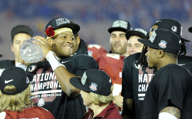 Jan 6, 2014; Pasadena, CA, USA; Florida State Seminoles quarterback Jameis Winston (5) pretends to pass the Coaches Trophy after the 2014 BCS National Championship game against the Auburn Tigers at the Rose Bowl.  Mandatory Credit: Kirby Lee-USA TODAY Sports