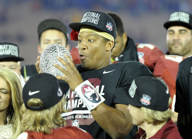 Jan 6, 2014; Pasadena, CA, USA; Florida State Seminoles quarterback Jameis Winston (5) pretends to drop the Coaches Trophy after the 2014 BCS National Championship game against the Auburn Tigers at the Rose Bowl.  Mandatory Credit: Kirby Lee-USA TODAY Sports