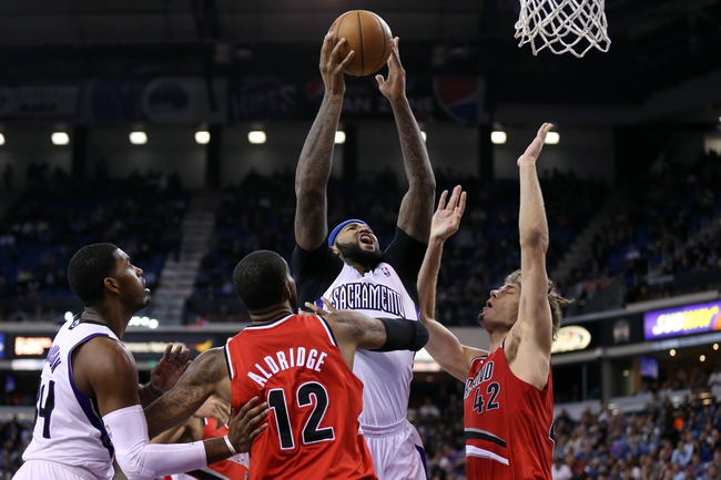 Jan 7, 2014; Sacramento, CA, USA; Sacramento Kings center DeMarcus Cousins (15) goes up for a shot between Portland Trail Blazers power forward LaMarcus Aldridge (12) and center Robin Lopez (42) during the third quarter at Sleep Train Arena. The Sacramento Kings defeated the Portland Trail Blazers 123-119. Mandatory Credit: Kelley L Cox-USA TODAY Sports