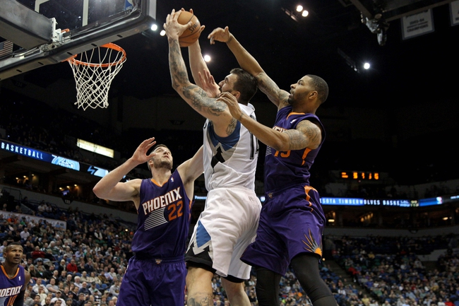 Jan 8, 2014; Minneapolis, MN, USA; Minnesota Timberwolves center Nikola Pekovic (14) grabs a rebound over Phoenix Suns center Alex Len (21) and forward Marcus Morris (15) during the third quarter at Target Center. The Suns defeated the Timberwolves 104-103. Mandatory Credit: Brace Hemmelgarn-USA TODAY Sports