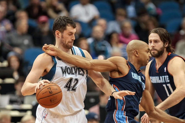 Jan 10, 2014; Minneapolis, MN, USA; Minnesota Timberwolves power forward Kevin Love (42) gets hit in the chest by Charlotte Bobcats guard Gerald Henderson (9) in the second quarter at Target Center. Mandatory Credit: Brad Rempel-USA TODAY Sports