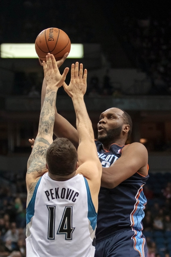 Jan 10, 2014; Minneapolis, MN, USA; Charlotte Bobcats center Al Jefferson (25) shoots in the second quarter against Minnesota Timberwolves center Nikola Pekovic (14) at Target Center. Mandatory Credit: Brad Rempel-USA TODAY Sports