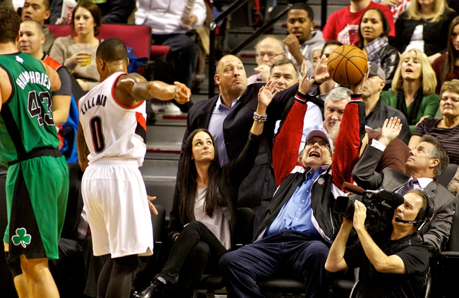 Jan 11, 2014; Portland, OR, USA; Portland Trail Blazers owner Paul Allen (center) and General manager Neil Olshey (right) reach for a ball that was knocked out of bounds during a game against the Boston Celtics at the Moda Center. Mandatory Credit: Craig Mitchelldyer-USA TODAY Sports