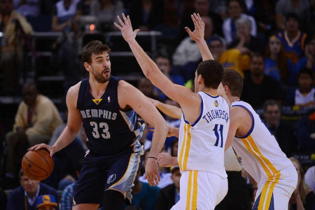 November 20, 2013; Oakland, CA, USA; Memphis Grizzlies center Marc Gasol (33) dribbles the basketball against Golden State Warriors shooting guard Klay Thompson (11) and power forward David Lee (10) during the fourth quarter at Oracle Arena. The Grizzlies defeated the Warriors 88-81 in overtime. Mandatory Credit: Kyle Terada-USA TODAY Sports
