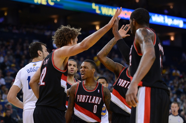 November 23, 2013; Oakland, CA, USA; Portland Trail Blazers point guard Damian Lillard (0) celebrates with his team during the fourth quarter against the Golden State Warriors at Oracle Arena. The Trail Blazers defeated the Warriors 113-101. Mandatory Credit: Kyle Terada-USA TODAY Sports