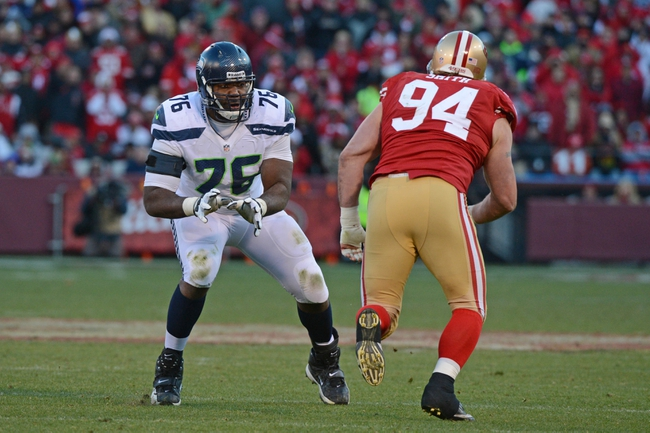 December 8, 2013; San Francisco, CA, USA; Seattle Seahawks tackle Russell Okung (76) blocks San Francisco 49ers defensive end Justin Smith (94) during the fourth quarter at Candlestick Park. The 49ers defeated the Seahawks 19-17. Mandatory Credit: Kyle Terada-USA TODAY Sports