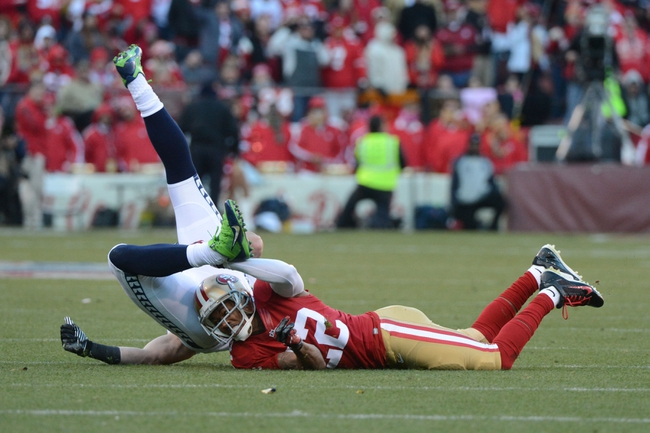 December 8, 2013; San Francisco, CA, USA; San Francisco 49ers cornerback Carlos Rogers (22, bottom) tackles Seattle Seahawks tight end Luke Willson (82, top) during the fourth quarter at Candlestick Park. The 49ers defeated the Seahawks 19-17. Mandatory Credit: Kyle Terada-USA TODAY Sports