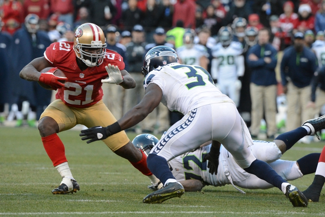 December 8, 2013; San Francisco, CA, USA; San Francisco 49ers running back Frank Gore (21) runs the football against Seattle Seahawks strong safety Kam Chancellor (31) during the fourth quarter at Candlestick Park. The 49ers defeated the Seahawks 19-17. Mandatory Credit: Kyle Terada-USA TODAY Sports