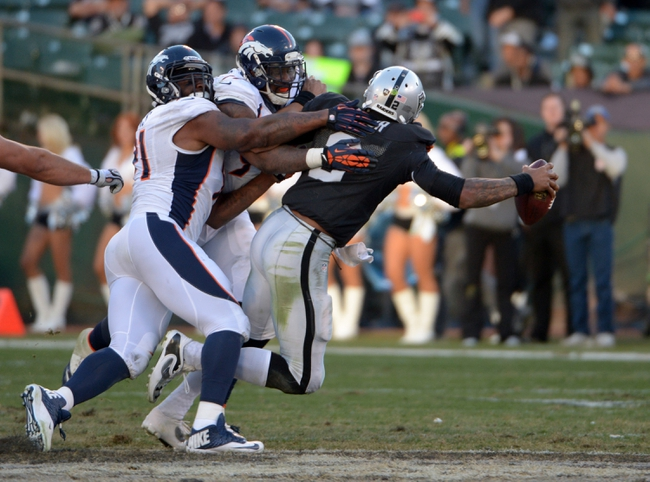 Dec 29, 2013; Oakland, CA, USA; Oakland Raiders quarterback Terrelle Pryor (2) is sacked by Denver Broncos defensive ends Malik Jackson (97) and Robert Ayers (91) at O.co Coliseum. The Broncos defeated the Raiders 34-14. Mandatory Credit: Kirby Lee-USA TODAY Sports