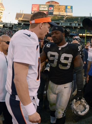 Dec 29, 2013; Oakland, CA, USA; Denver Broncos quarterback Peyton Manning (18) shakes hands with Oakland Raiders defensive end Lamarr Houston (99) after the game at O.co Coliseum. The Broncos defeated the Raiders 34-14. Mandatory Credit: Kirby Lee-USA TODAY Sports