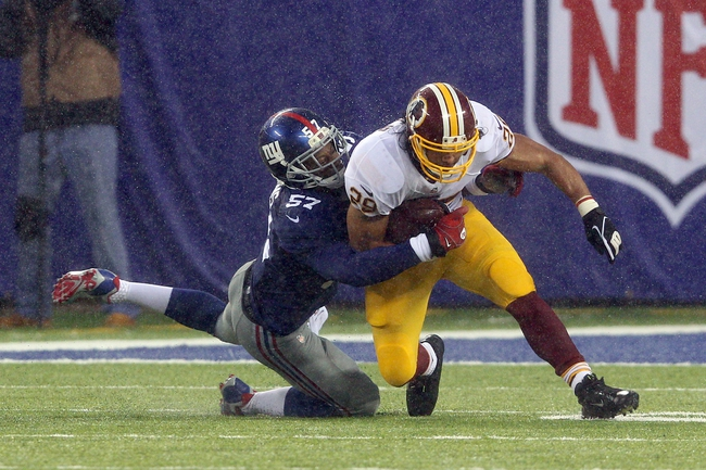 Dec 29, 2013; East Rutherford, NJ, USA; Washington Redskins running back Roy Helu (29) is tackled by New York Giants linebacker Jacquian Williams (57) during a game at MetLife Stadium. The Giants defeated the Redskins 20-6. Mandatory Credit: Brad Penner-USA TODAY Sports