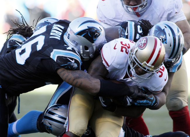Jan 12, 2014; Charlotte, NC, USA; San Francisco 49ers running back Kendall Hunter (32) is brought down by Carolina Panthers defensive end Greg Hardy (76) during the second half of the 2013 NFC divisional playoff football game at Bank of America Stadium. Mandatory Credit: Jeremy Brevard-USA TODAY Sports