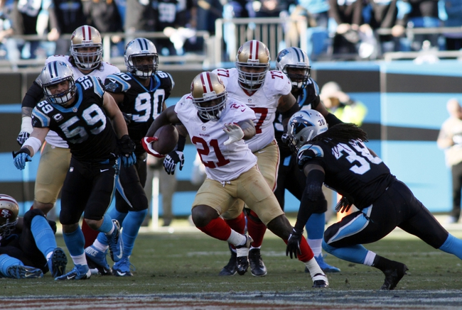 Jan 12, 2014; Charlotte, NC, USA; San Francisco 49ers running back Frank Gore (21) runs against Carolina Panthers strong safety Robert Lester (38) during the second half of the 2013 NFC divisional playoff football game at Bank of America Stadium. Mandatory Credit: Jeremy Brevard-USA TODAY Sports